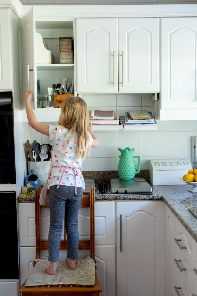 girl accessing kitchen cabinet shelf